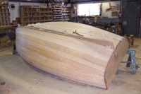 The hull is faired, caulked with cotton, plugged, and sanded.