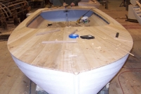Cedar planking is nailed to the deck structure, faired, and filled.